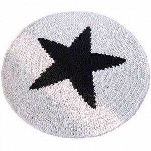 Musta tähti kuvioituna virkattuun mattoon