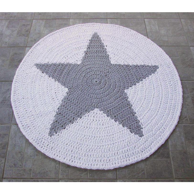 Harmaa tähti virkattuna valkean maton keskustaan