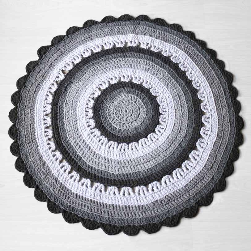 Kauniisti sommiteltu harmaa virkattu matto