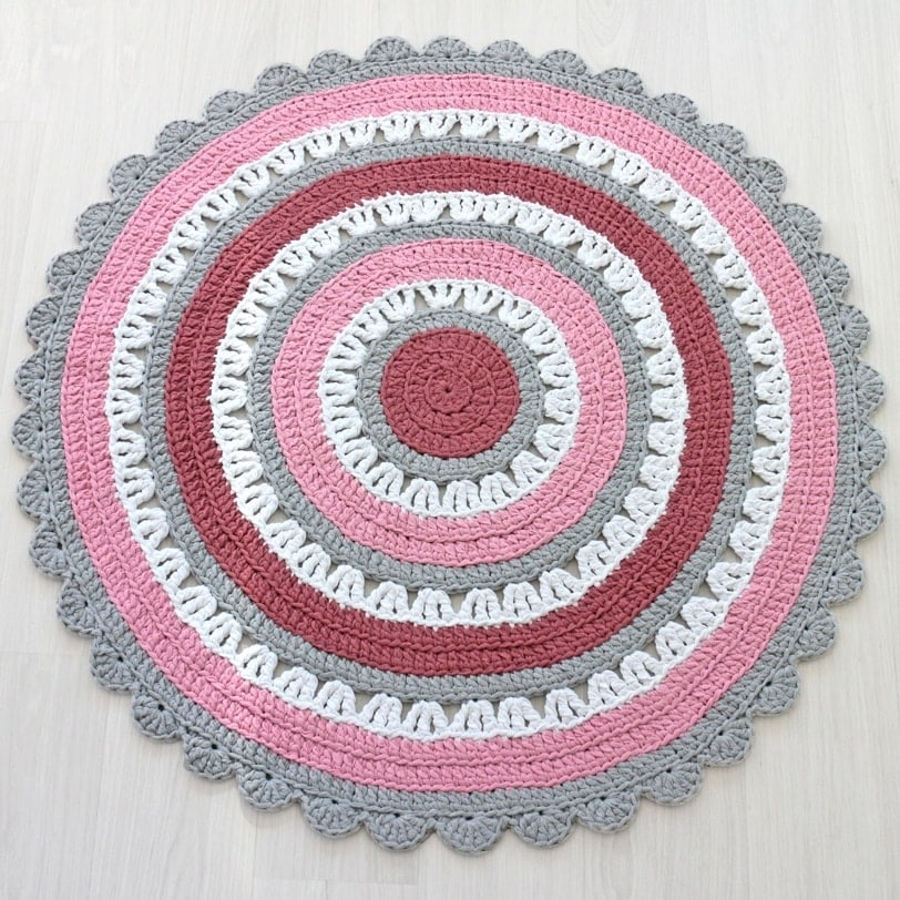 vaaleanpunaisen ja harmaan väriyhdistelmästä virkattu matto